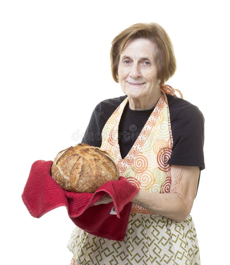 Бабушка с свежим испеченным ломтем хлеба стоковые изображения