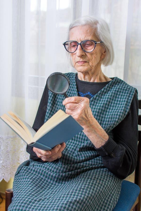 Бабушка читая книгу через лупу стоковое фото rf