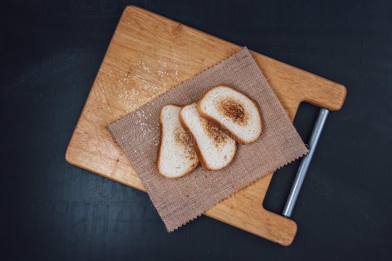 Багет здравицы на шифере Провозглашанный тост хлеб Хлеб бел на черной предпосылке Хлеб на деревянной предпосылке стоковые фото
