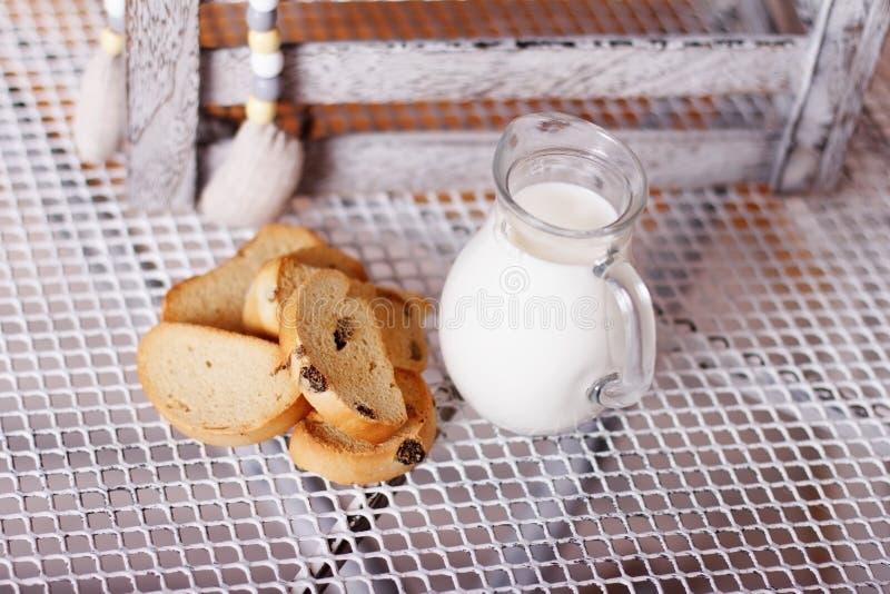 Багет и молоко в кувшине на таблице стоковые фото