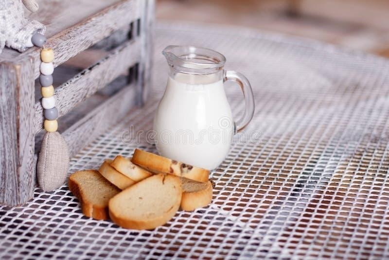 Багет и молоко в кувшине на таблице стоковое фото rf