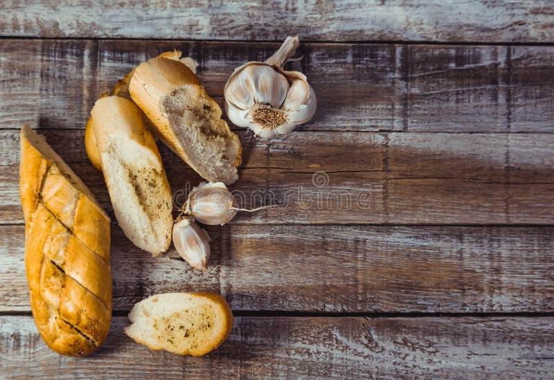 Багет с маслом чеснока, ароматичными травами и куском чеснока на деревянной предпосылке Фотография еды взгляда сверху стоковая фотография rf