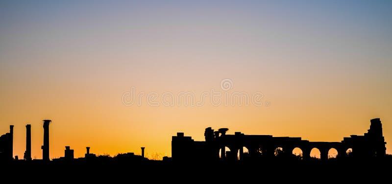 Базилика места Volubilis римские и силуэт захода солнца капитолия стоковые изображения