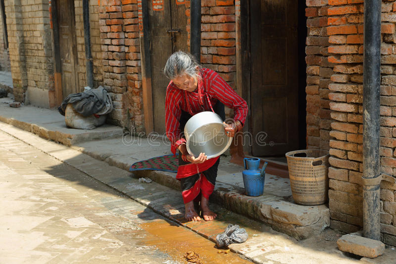 Баки индусской старухи моя в городке Bhaktapur, Непале стоковые фото