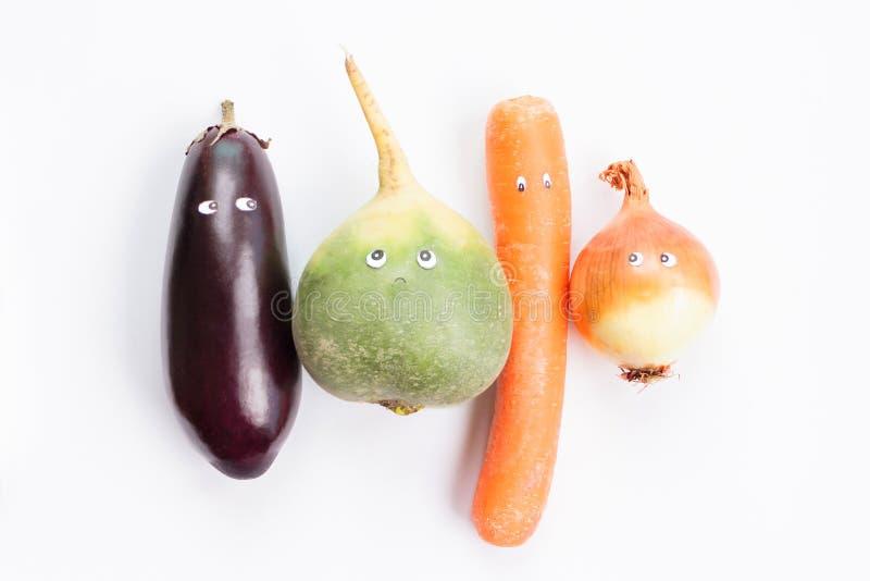Баклажан, зеленая редиска, морковь, лук-порей с шаржем наблюдает на белой предпосылке стоковое фото