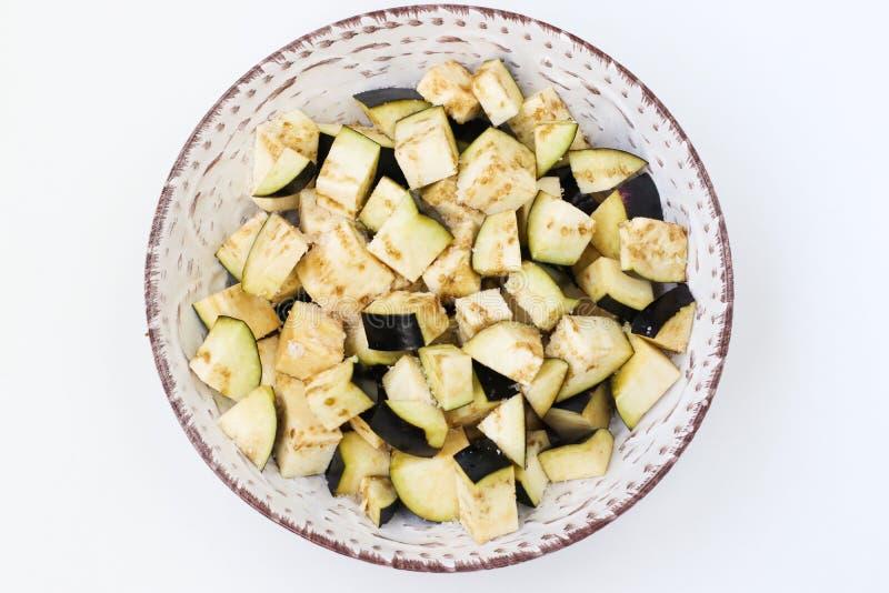 Баклажан отрезал в кубы для салата, помещенные в плите на белой предпосылке, взгляд сверху стоковые изображения rf