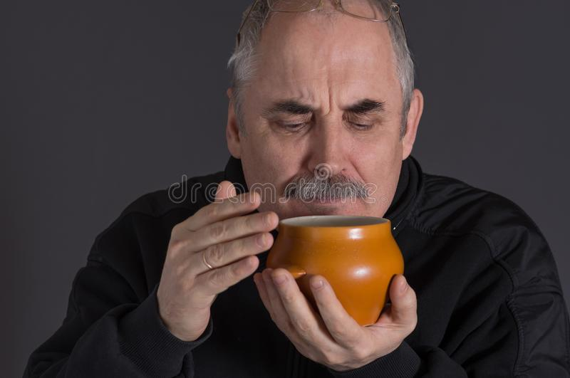 Бак агашка кавказского человека пахнуть с едой против темной предпосылки стоковые изображения rf