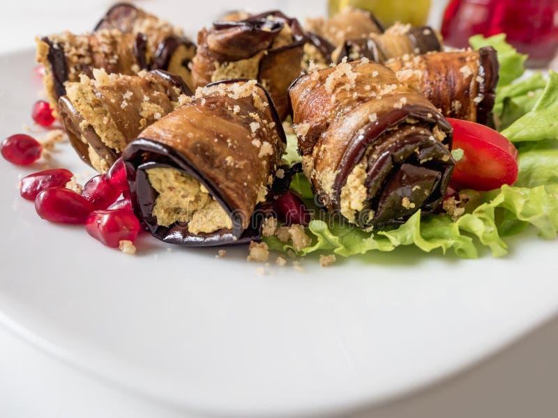 Баклажан свертывает с грецкими орехами Очень вкусные зажаренные aubergines с гайками, травами и семенами гранатового дерева Блюдо стоковые изображения rf