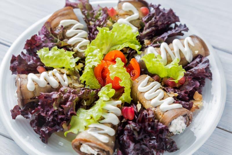 Баклажан свертывает с сыром, чесноком и белый соус и салат салата выходят Белая чернота и деревянный стол изображение наушников ч стоковая фотография