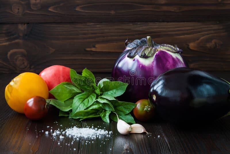 Баклажан (aubergine) с базиликом, чесноком и томатами на темном деревянном столе Свежие сырцовые овощи фермы - сожмите от стоковые изображения