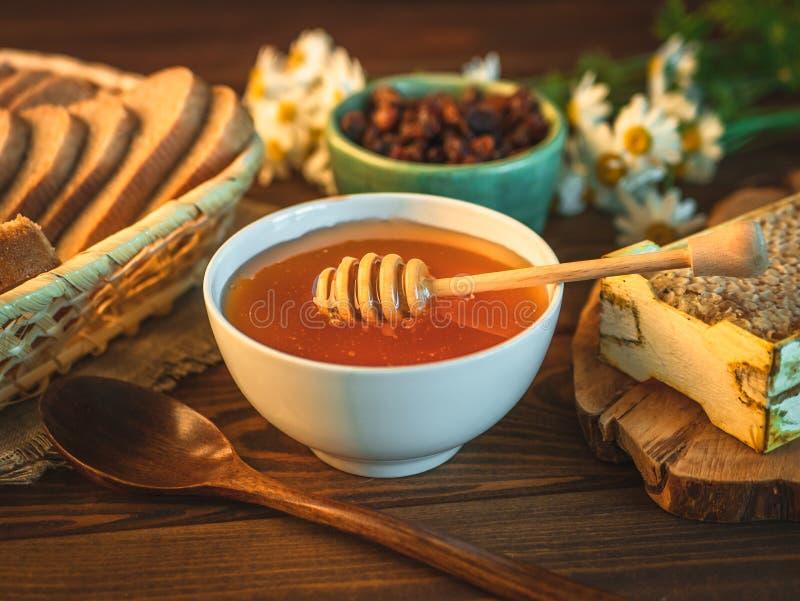 Бак и ковш меда на деревенской таблице с хлебом, изюминками, стоцветом и гребнем меда стоковые фотографии rf