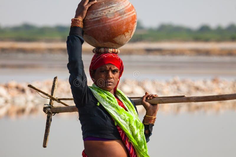 Бак нося индийской женщины на голове стоковое фото rf