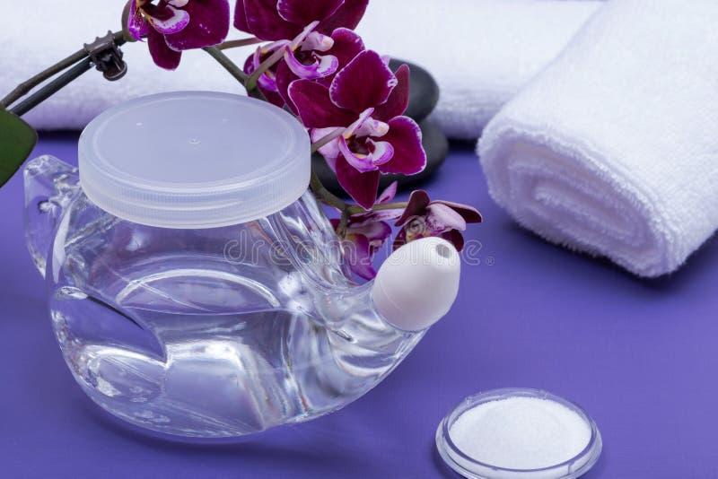 Бак с мягкой подсказкой комфорта, куча Neti соляных, пурпурных цветков орхидеи и свернутый вверх по белым полотенцам на пурпурной стоковые фото