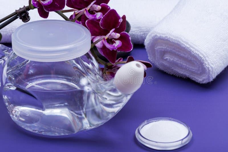 Бак с мягкой подсказкой комфорта, куча Neti соляных, пурпурных цветков орхидеи и свернутый вверх по белым полотенцам на пурпурной стоковое изображение rf