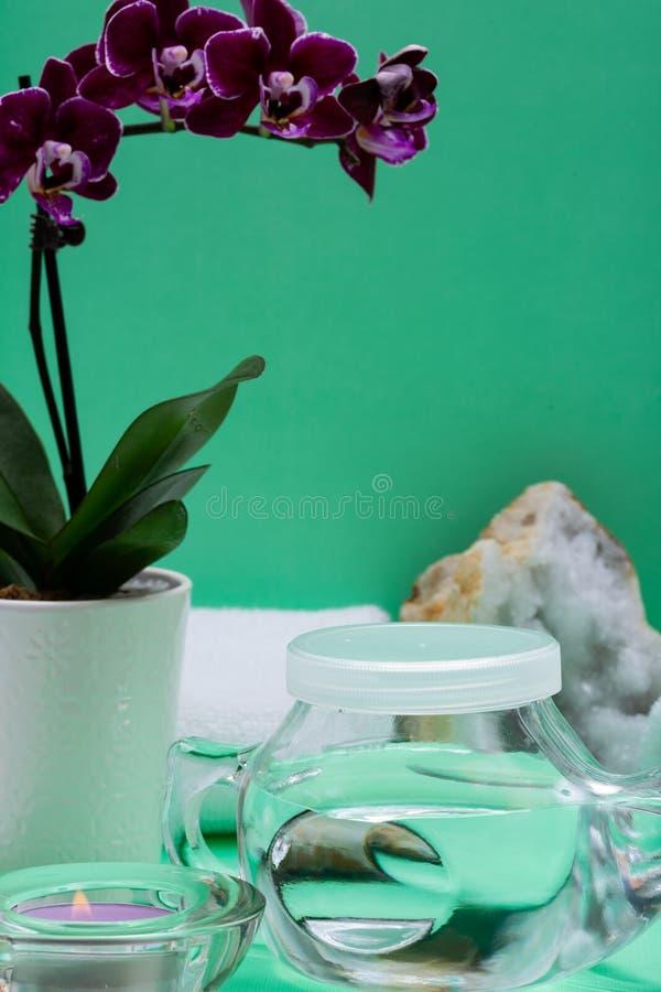 Бак Neti, куча соляных, свернутых белых полотенец, пурпурных цветков орхидеи и свечи света чая лаванды на зеленой предпосылке Мыт стоковое фото