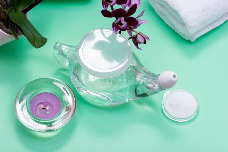 Бак Neti, куча соляных, свернутых белых полотенец, пурпурных цветков орхидеи и свечи света чая лаванды на зеленой предпосылке Мыт стоковое изображение