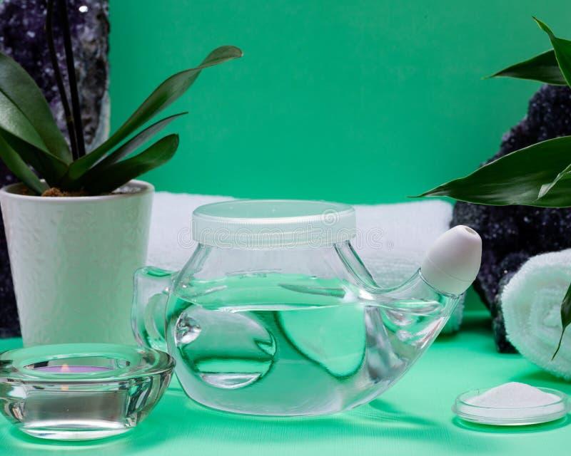 Бак Neti, куча соляных, свернутых белых полотенец, пурпурных цветков орхидеи и свечи света чая лаванды на зеленой предпосылке Мыт стоковые фото