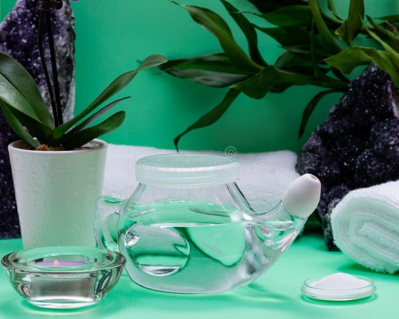 Бак Neti, куча соляных, свернутых белых полотенец, пурпурных цветков орхидеи и свечи света чая лаванды на зеленой предпосылке Мыт стоковые изображения rf