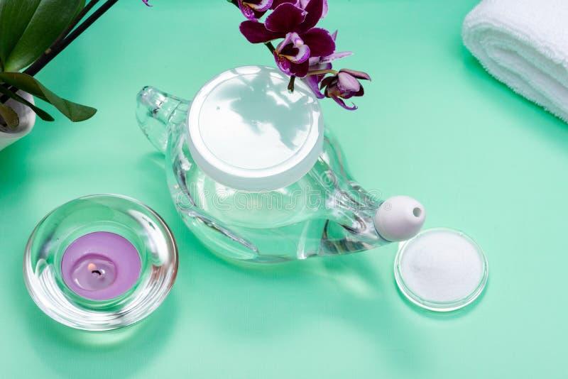 Бак Neti, куча соляных, свернутых белых полотенец, пурпурных цветков орхидеи и свечи света чая лаванды на зеленой предпосылке Мыт стоковые изображения