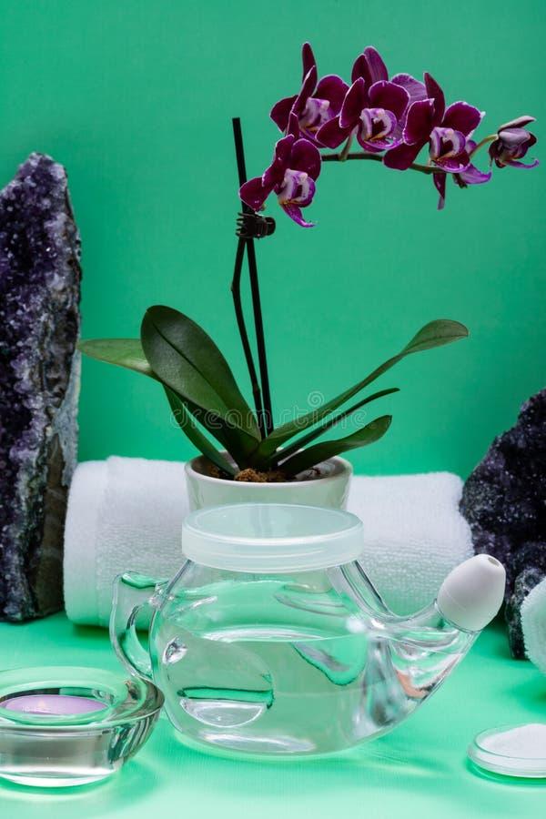 Бак Neti, куча соляных, свернутых белых полотенец, пурпурных цветков орхидеи и свечи света чая лаванды на зеленой предпосылке Мыт стоковые фотографии rf