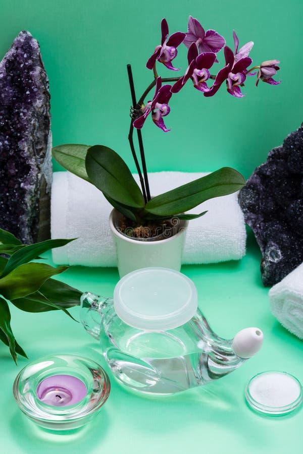 Бак Neti, куча соляных, свернутых белых полотенец, пурпурных цветков орхидеи и свечи света чая лаванды на зеленой предпосылке Мыт стоковое фото rf