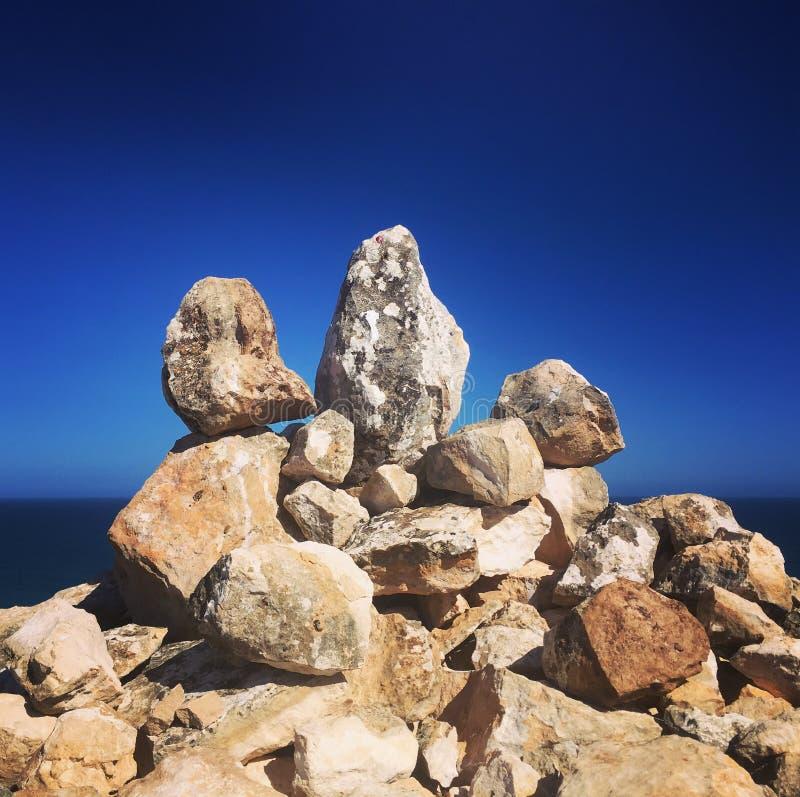 Балансировать трясет против голубого фона океана и неба стоковая фотография