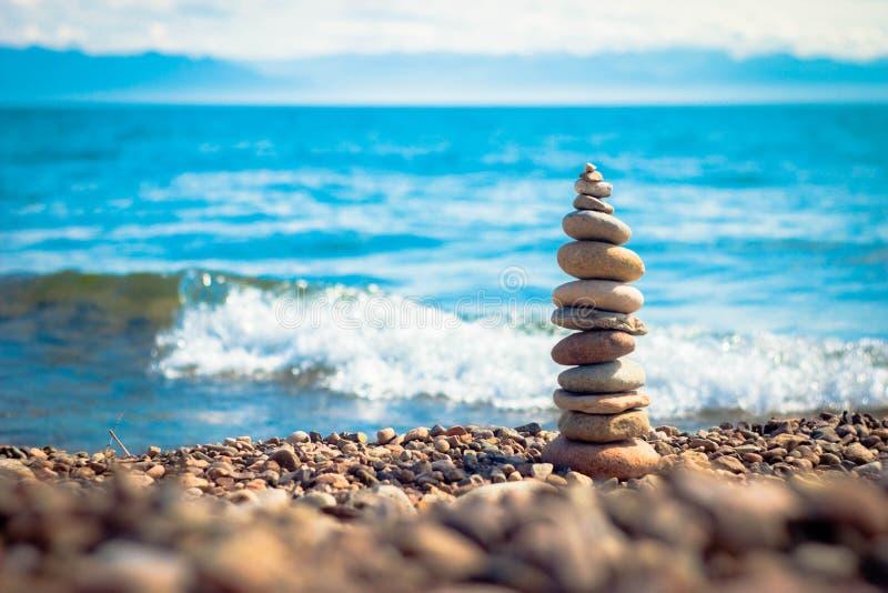 Балансируя камни на предпосылке причаливая волны стоковые изображения rf