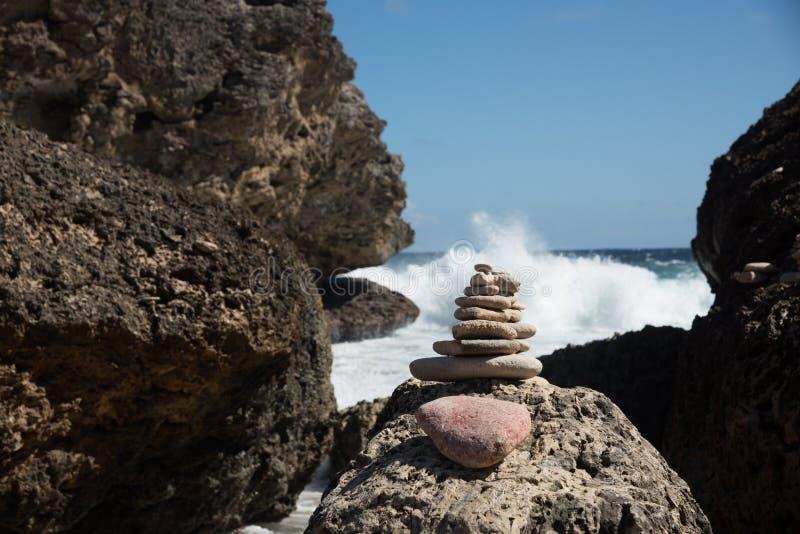 Балансируя утесы перед океанскими волнами стоковая фотография