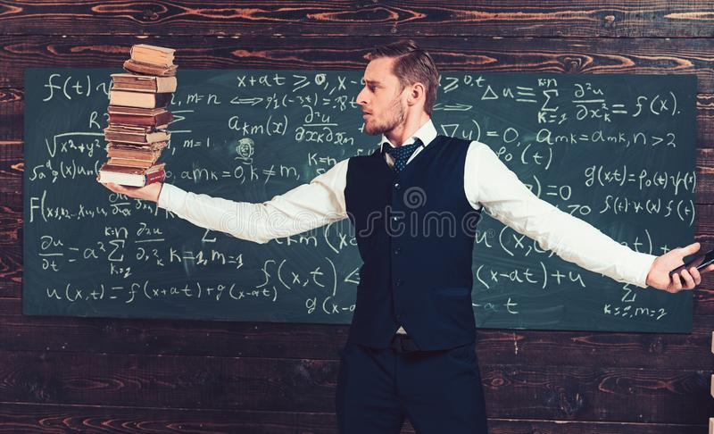 Баланс между технологией и знанием Белокурый парень в костюме держа кучу книг в одной руке и смартфоне внутри стоковые изображения rf