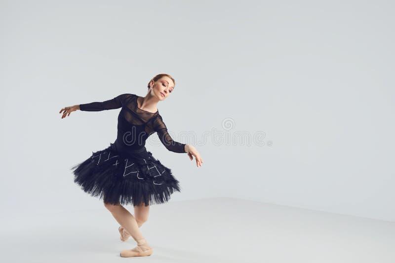 Балерина в черной балетной пачке элегантно танцуя на черной предпосылке стоковые фото