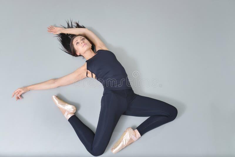 Балерина молодой женщины лежа и протягивая на поле на студии балета, осматривает сверху стоковое изображение