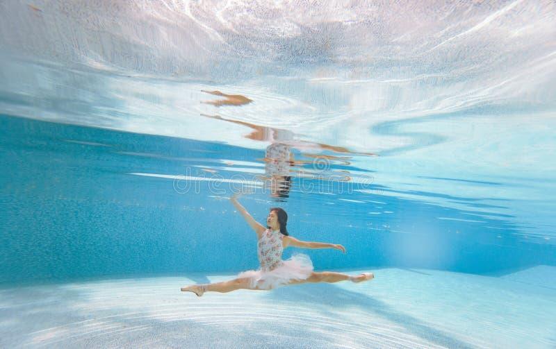 Балерина танцует под водой и делает шпагат стоковые фото