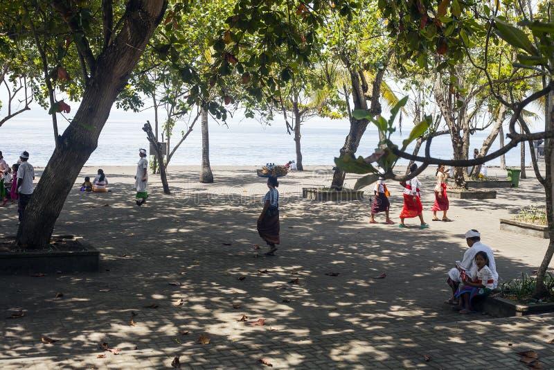 Балийские люди в традиционных одеждах около голубого океана стоковые фото