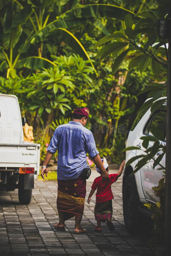 БАЛИ, ИНДОНЕЗИЯ - 13-ОЕ АПРЕЛЯ 2018: Азиатский ребенк с его отцом на балийский день свадьбы Индонезийский ребенок стоковые фотографии rf