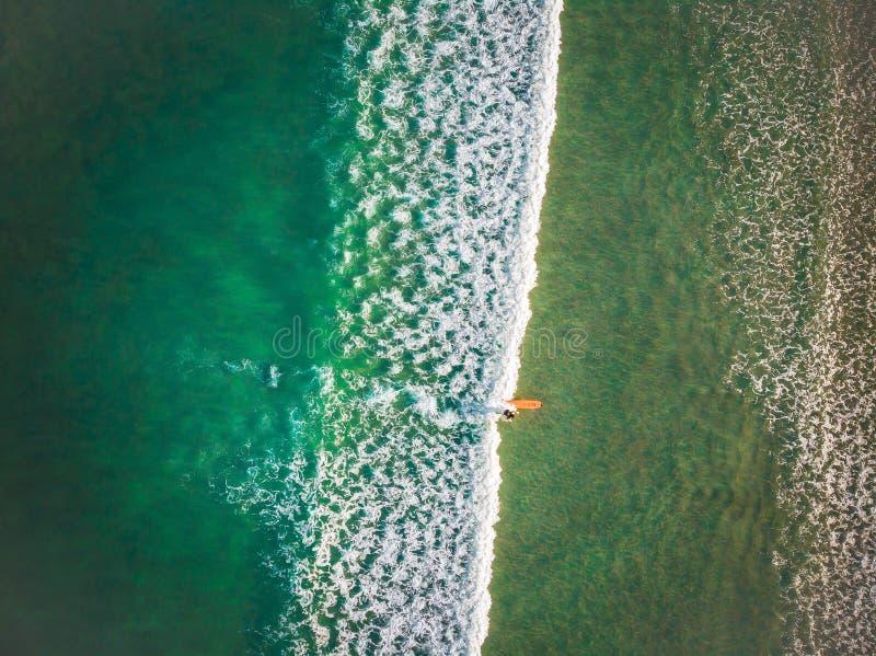 Бали, Индонезия - 12-ое апреля 2018: Вид с воздуха людей занимаясь серфингом на Kuta приставает к берегу, Бали стоковая фотография