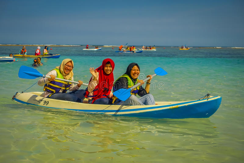 БАЛИ, ИНДОНЕЗИЯ - 11-ОЕ МАРТА 2017: Неопознанные люди наслаждаясь красивым солнечным днем над каяком в пляже  стоковая фотография rf