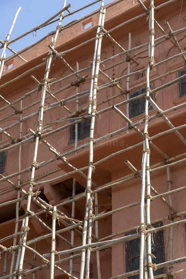 Бамбуковая ремонтина на доме, реновации Леса на здании, розовой стене и окне Джайпур, Индия стоковое фото rf