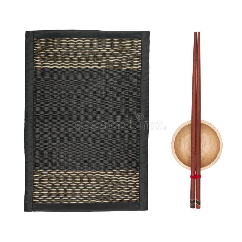 Бамбуковая циновка для еды и чашки места с палочками на белой предпосылке стоковые фото