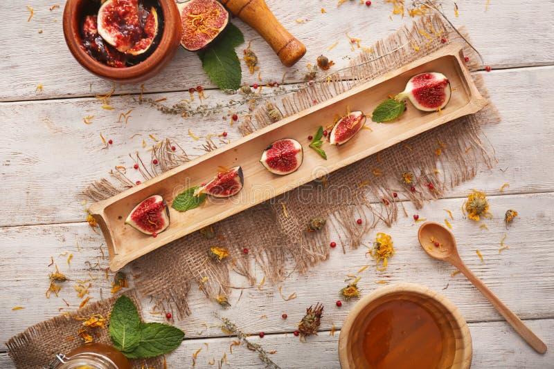 Бамбуковый поднос с отрезанными зрелыми смоквами на деревянной предпосылке стоковая фотография rf