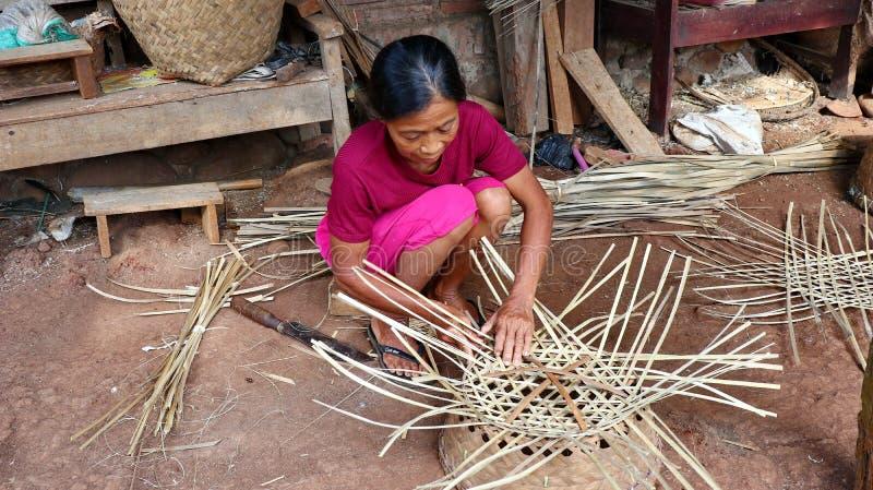Бамбуковый craftswoman корзины пока делающ его работу стоковая фотография