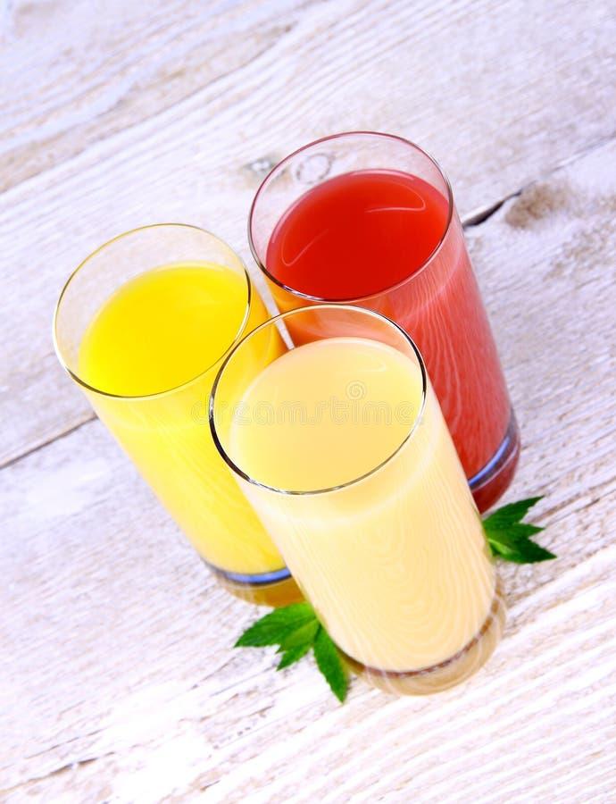 Бананы, апельсины и красный сок в стекле стоковое фото rf