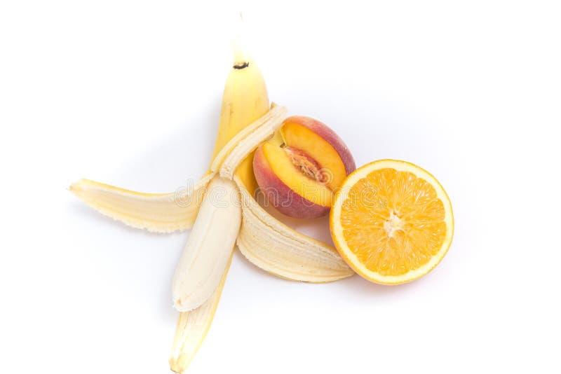 Банан, персик и апельсин на белизне стоковая фотография