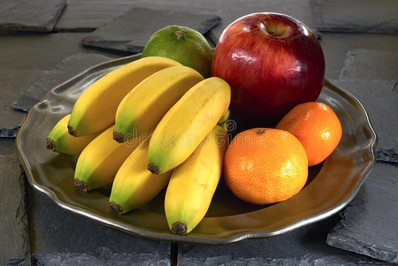 Банан, яблоко и мандарин на металлической пластине, на черном камне шифера стоковое изображение rf