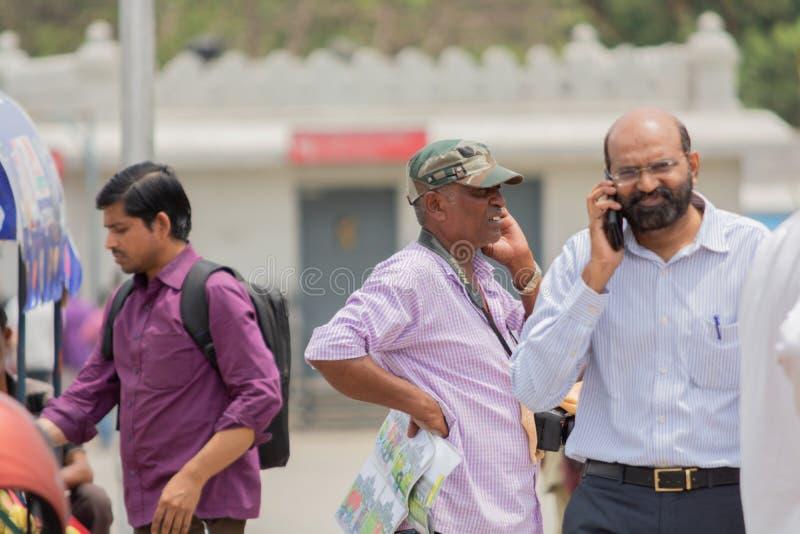 Бангалор, Karnataka Индия 4-ое июня 2019: Люди занятые в говорить на мобильном телефоне или мобильном телефоне на Bengaluru, Karn стоковые фотографии rf