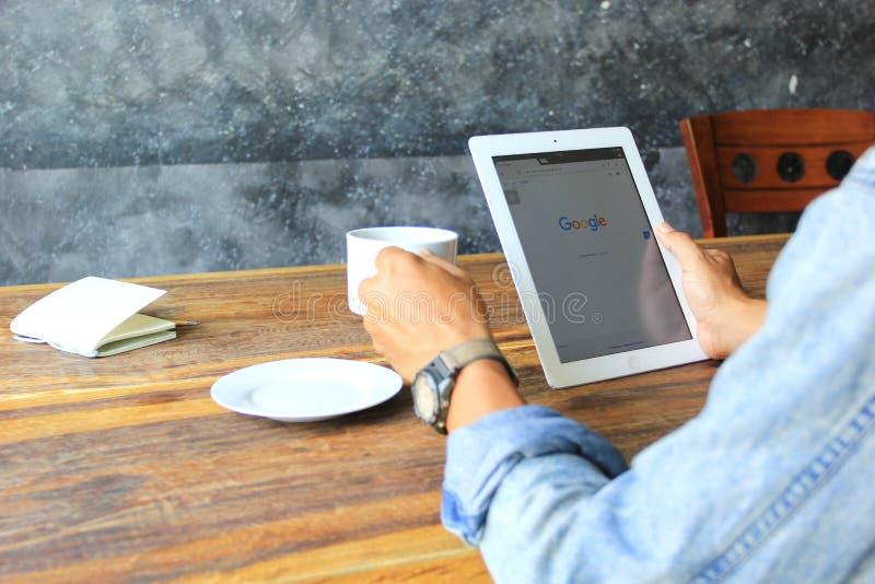 Бангкок, Таиланд: Джейн 3, 2018, рука человека используя прибор ipad умный с Google поиска домашней страницы и руки чашкой кофе у стоковые фотографии rf