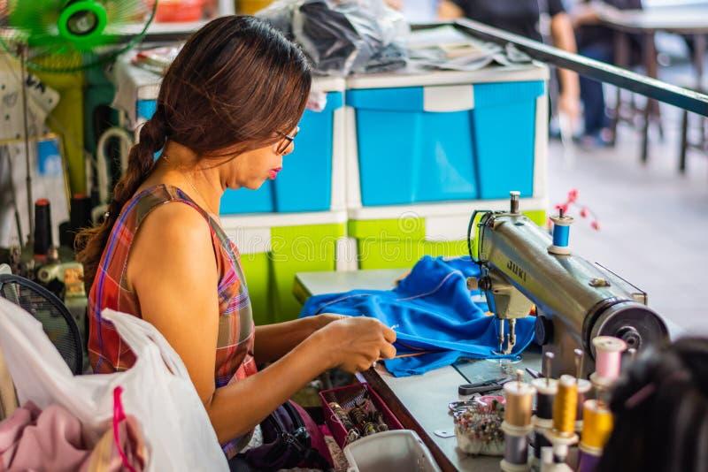 БАНГКОК, ТАИЛАНД - НОЯБРЬ 2018: Женщина шить на швейной машине руководя магазин портноя на улице в Бангкоке, Таиланде стоковые фотографии rf