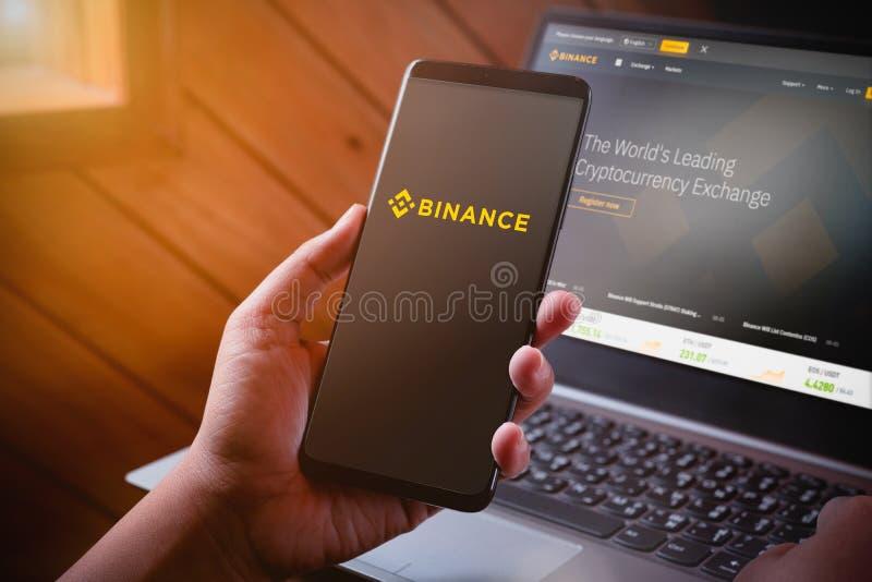 Бангкок, Таиланд - 5-ое августа 2019: Руки держа смартфон с логотипом binance на экране и вебсайте binance на предпосылке ноутбук стоковое изображение