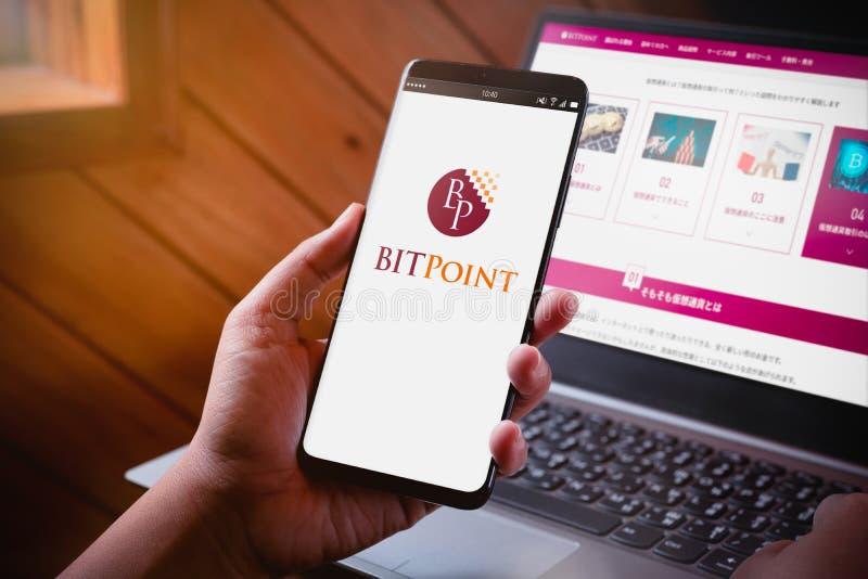 Бангкок, Таиланд - 6-ое августа 2019: Руки держа смартфон с экраном логотипа BitPoint и вебсайтом BitPoint на предпосылке ноутбук стоковое изображение