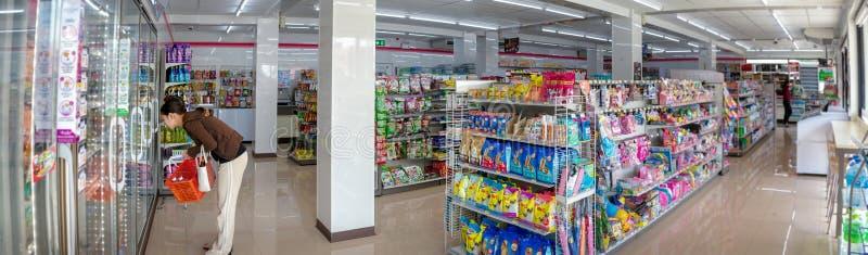 БАНГКОК, ТАИЛАНД - 24-ОЕ АПРЕЛЯ: Безымянные женские магазины клиента в заново раскрытом удобном магазине 7-Eleven в площади Chao  стоковая фотография rf