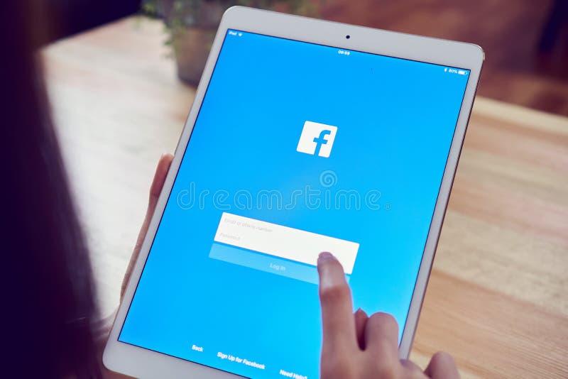 Бангкок, Таиланд - 19-ое апреля 2018: рука отжимает экран Facebook на ipad яблока pro стоковые изображения